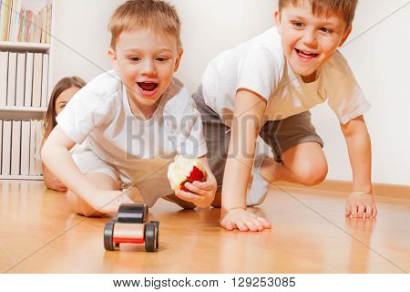 Happy kids, two brothers, playing with wooden toy car at the floor, chasing each other