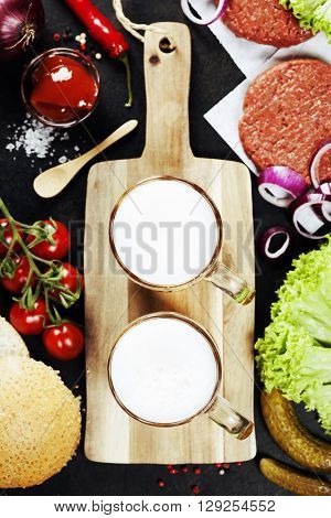 Beer and Raw Ground beef meat Burger steak cutlets with seasoning and vegetables on vintage background