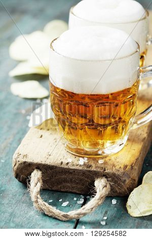 Beer and Potato Chips on vintage wooden table