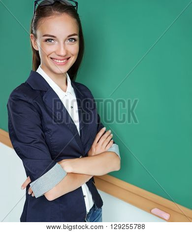 Attractive student folded arms near blackboard. Photo of young student creative concept with Back to school theme