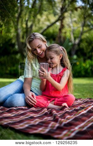 Smiling daughter showing phone to mother while sitting in yard