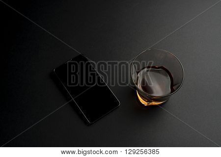 Smartphone and cognac on a black table background