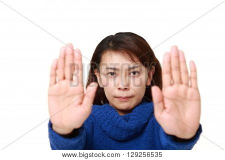Asian woman making stop gesture on white background
