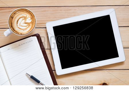 Office workplace with blank screen tablet notebook pen and coffee cup on rustic wood table.Top view