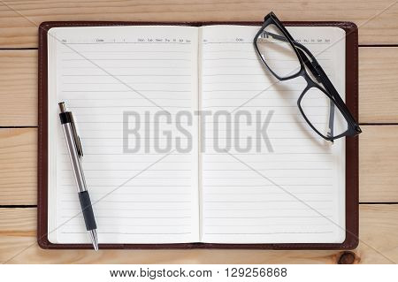 Office workplace with notecook eye glasses and pen on rustic wood table.Top view