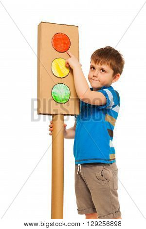 Boy studying road traffic rules, pointing to the red light of cardboard lights model, isolated on white