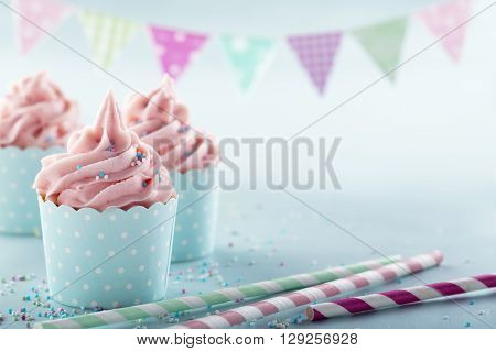 Pink frosted cupcakes on light blue background