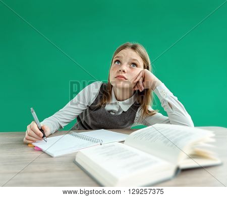 Fantasy pupil looking up as if daydreaming or thinking of something while sitting at the desk with open book. Photo of teen school girl creative concept with Back to school theme