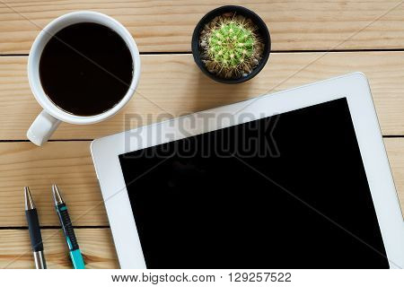 Office stuff with blank screen tabletpenpencil and coffee cup on rustic wood table.Top view