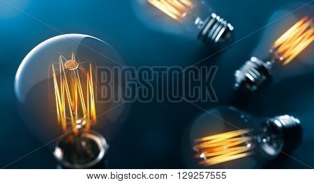 Glowing Edison light bulb on blue background