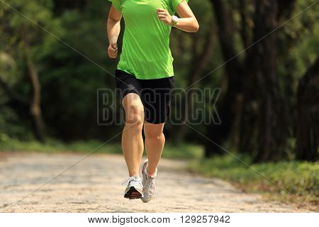 one woman trail runner running on forest trail