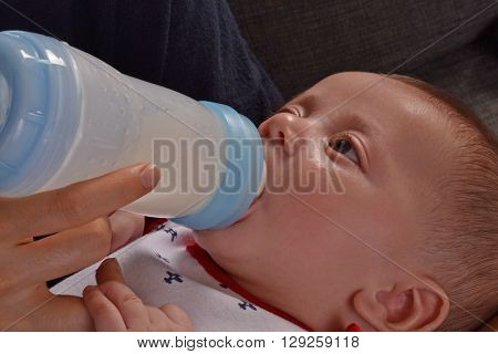Mother feeding her close up baby boy with a plastic baby bottle.
