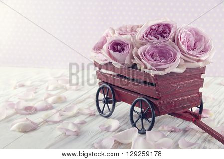 Purple rose bouquet in a decorative wooden carriage on wooden vintage background