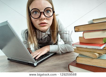 Schoolgirl at a loss working with computer. Photo of teen with laptop creative concept with Back to school theme