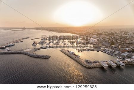 Aerial view of fishing boats docked at the Limassol old port (palio limani) in Cyprus at sunset next to the Marina part of the ports authority. A view of the harbor the mediterranean sea the water boat and fish nets and fishing equipment.