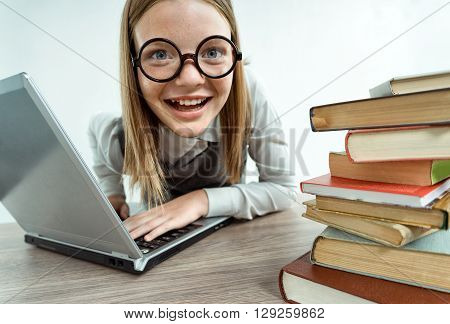Happy smiling school girl at the classroom working with computer. Photo of smiling teen creative concept with Back to school theme