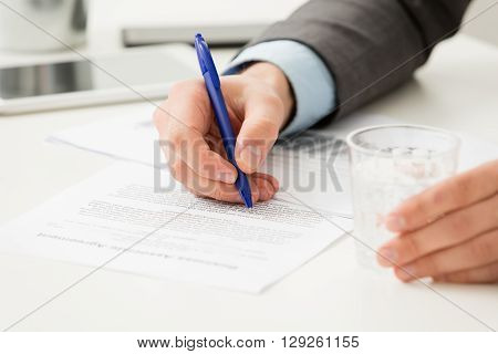 Close up of businessman signing contract with blue ballpoint pen