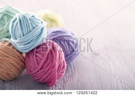 Pastel yarn balls on pink wooden vintage background