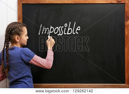 Schoolgirl near blackboard with word impossible transformed into possible