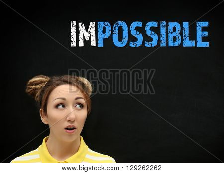 Young woman near blackboard with word impossible transformed into possible