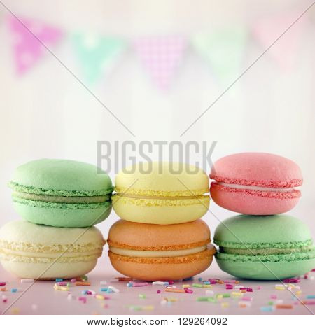 Colourful small macarons with pink pastel background