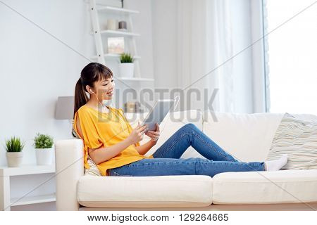 people, technology and leisure concept - happy asian young woman sitting on sofa with tablet pc computer and earphones listening to music at home