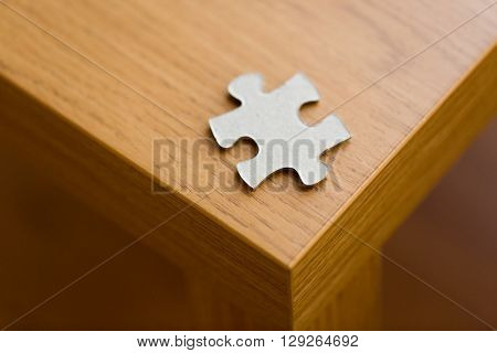 business and connection concept - close up of puzzle piece on wooden surface
