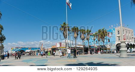 Venice Beach, USA - October 6, 2015: Tourists stroll boardwalk  in front the tacky shops and cheap signs under bright blue Californian sky Venice Beach CaliforniaCalifornia