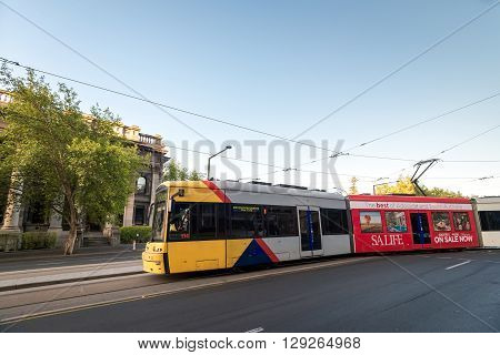 Adelaide Australia - January 3 2016: Famous Adelaide tram turning from King William street to North Terrace and heading to the Entertainment Centre on the summer evening.