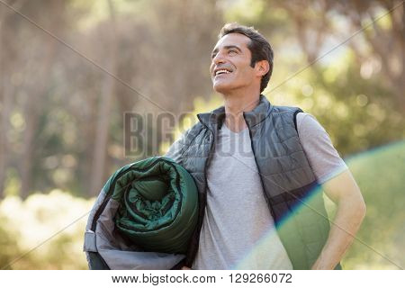 Man smiling and holding a sleeping bag on the wood