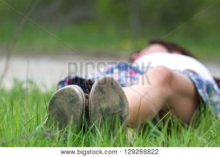 Macro photo of shoe soles. Girl resting on nature after a long physical activity