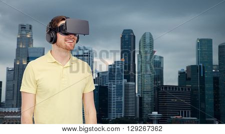 3d technology, virtual reality, travel, entertainment and people concept - happy young man with virtual reality headset or 3d glasses over singapore city skyscrapers background
