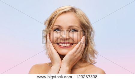beauty, people and skincare concept - smiling woman with bare shoulders touching face over rose quartz and serenity gradient background