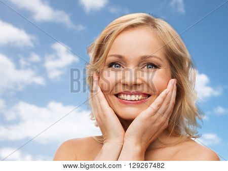 beauty, people and skincare concept - smiling woman with bare shoulders touching face over blue sky and clouds background
