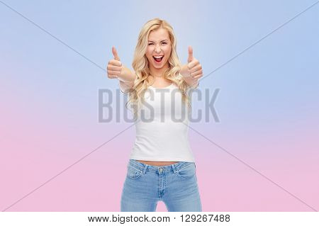 emotions, expressions, advertisement and people concept - happy smiling young woman or teenage girl in white t-shirt showing thumbs up with both hands over rose quartz and serenity gradient background