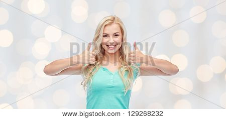 positive gesture and people concept - smiling young woman or teenage girl showing thumbs up with both hands over holidays lights background