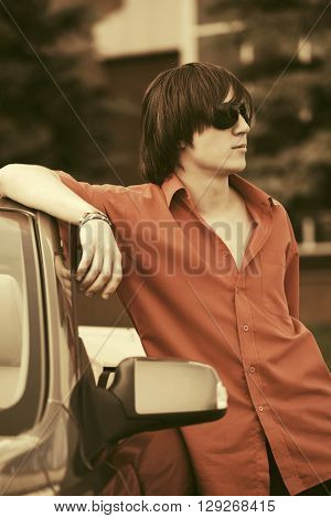 Young fashion man in sunglasses leaning on his convertible car. Male fashion model outdoor
