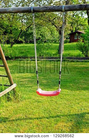 Garden red plastic children's swing in the garden playtime