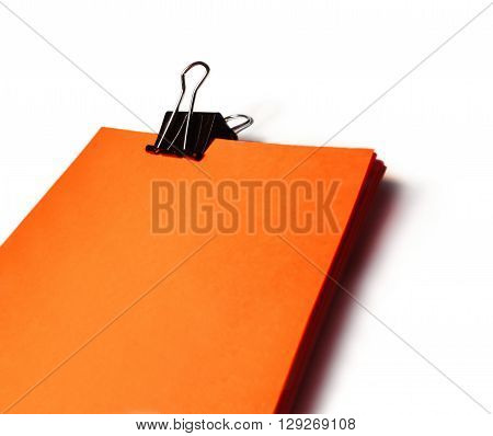 orange colored paper with paper clip, isolated on White