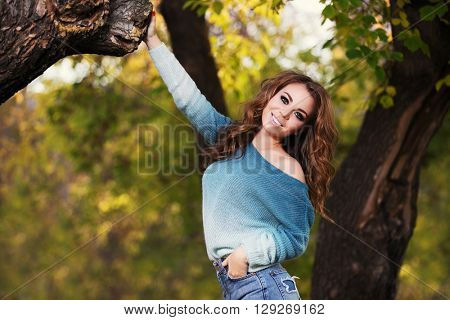 Happy young fashion woman with long curly hairs walking in city park. Female fashion model outdoor