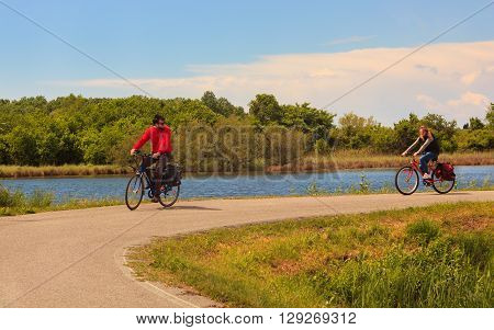 GRADO ITALY - APRIL 25: Couple cycling in the Nature reserve of the Isonzo river mouth on April 25 2016