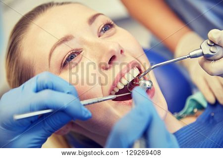 people, medicine, stomatology and health care concept - close up of dentists and assistant with mirror, drill and dental air water gun spray treating female patient teeth at dental clinic