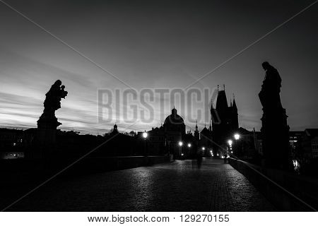 Charles Bridge at sunrise, Prague, Czech Republic. Dramatic statues and medieval towers. Unique view at dawn when there are almost no people on the bridge. Black and white