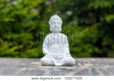 Buddha - ceramic statuette buddha on green background. Buddhism, meditation and yoga concept.
