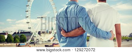 people, homosexuality, same-sex marriage, travel and love concept - close up of happy male gay couple hugging from back over london ferry wheel background