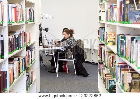 VILNIUS LITHUANIA - APRIL 23 2016: Two young female students sitting and studying at Vilnius University library Lithuania