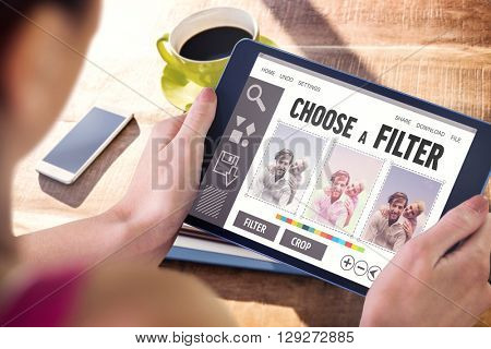 Woman using tablet pc against cup of coffee and tablet pc