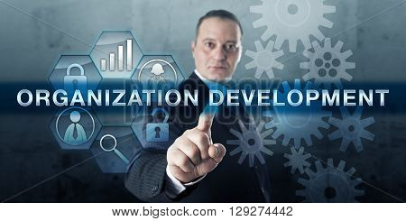 Entrepreneur is pushing ORGANIZATION DEVELOPMENT on an interactive touch screen display. Business concept for the expansion of knowledge and effectiveness of workers aimed at organizational success.