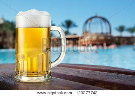 Mug of light beer outdoor. Near the swimming pool.