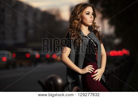 Young fashion woman on night city street. Female fashion model with long curly hairs outdoor